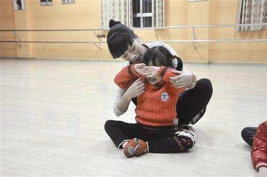 童星之路充满艰辛。一位在舞蹈班学习的小朋友练习压胯动作痛得大哭
