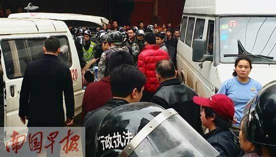 受伤摊贩被城管人员抬上救护车。