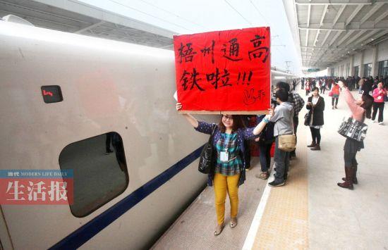 3月19日,广西梧州南站,高兴的梧州市民举牌庆祝高铁通车。记者 何学俏 摄