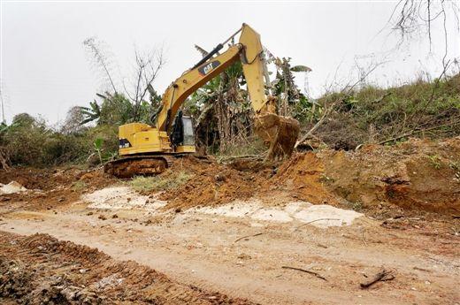 勾机正在对邕宾路广西烈士陵园北门前的滑坡泥土进行清理。