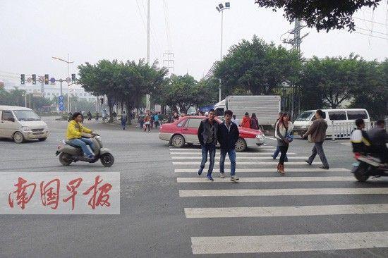 科园大道与科园西十路交叉路口,一辆左转的红色出租车将行人队伍挡住。