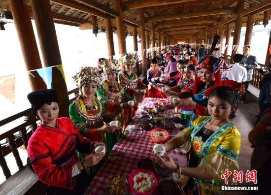 4月2日,各外地游客和当地群众一同在广西龙胜各族自治县民族风雨桥吃百家宴。中新社发 韦吉阳 摄