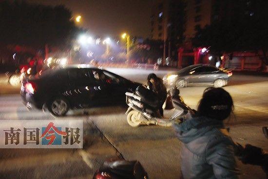 被打的叶女士狼狈地从地上爬起来,并扶起自己的电动车。