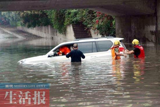 北海市昨日突发暴雨,数辆小车遇积水熄火,消防队员先后救出11位被困人员。图为当地四川路铁路桥下的被困车辆。通讯员 范辉宝 摄