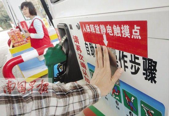 一车手触摸自助加油机上的装置,释放静电。