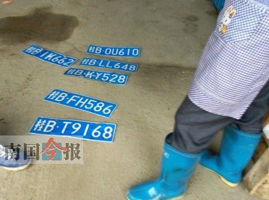 周围居民拿出从泥水中打捞的车牌。