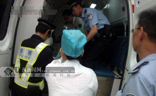 民警与医务人员用担架将女子搬运上救护车。南宁市公安局巡警支队供图