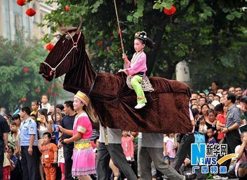 """演员在民俗巡游中表演传统民俗""""三人马"""""""