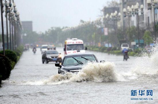 河池市凤山县县城,车辆在内涝的街道上行驶。