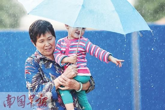 4月9日下午4时,南宁市下起阵雨。长堽路边,市民冒雨前行。记者 邹财麟摄