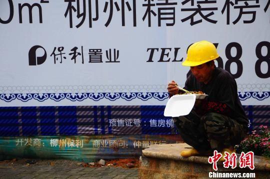4月10日,柳州市一大型房地产开发工地旁,农民工劳作后在吃快餐。 雷彬 摄