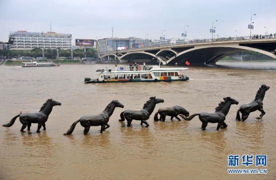 """4月11日,在漓江桂林市区解放桥河段,游船从被部分淹没的""""六匹马""""景点前经过。"""