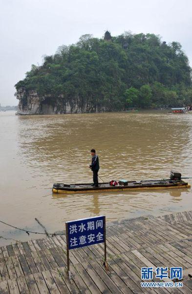 4月11日,在漓江桂林市区象山景区河段,一名市民划着竹筏从暴涨的河水中经过。