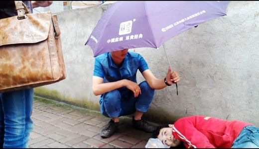 穿蓝色衣服的男子为倒地的女子撑伞挡雨