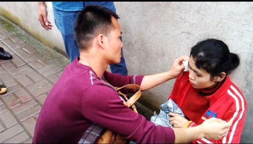 穿着紫色T恤的男子为该女子擦去脸上的泥沙