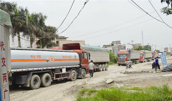 大量超载车辆从过道上经过,是道路变泥潭的主要原因。图片来源:南国早报