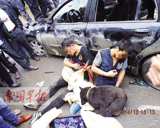 """图为两名男子涉嫌偷狗被打后,抱着死狗示众。 网友""""hxl15446206""""摄"""