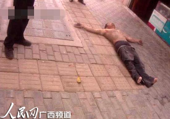 周某赤裸上身躺在地上。