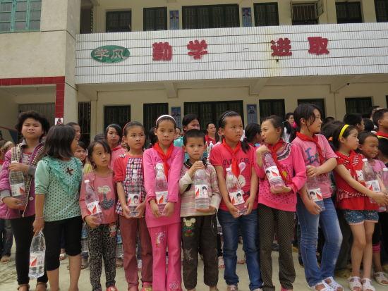 弄新小学的孩子们收到娃哈哈等爱心企业送来的饮用水。来源:新浪广西