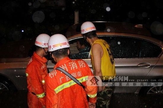消防员正在帮助车主从车上下来。图片来源:广西新闻网