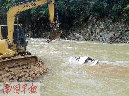 救援人员用钩机将失事小车从河中吊起。黄訸摄