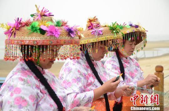 身着传统疍家服饰的渔妇娴熟地织网。翟李强 摄