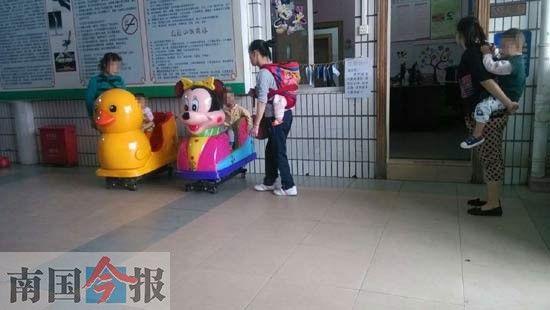 在家长的看护下,两名小朋友正坐在摇摇车上,玩得不亦乐乎。记者伍蹈 摄