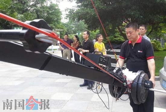 """柳州市青少年宫童声合唱歌曲MV拍摄现场,""""草根""""团队57岁的摄影师张辛谊在操作大摇臂摄像机。"""