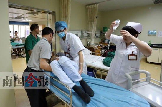 男护士金宣磊和患者家属正在将一名老人抬到平车上,与女护士相比,男护士体力上更占优势。