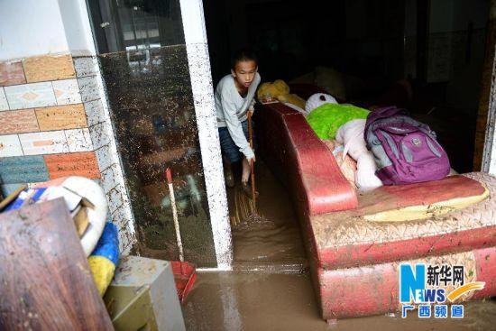 5月11日,在广西昭平县城一处居民区,居民在清理涌进屋中的泥浆。