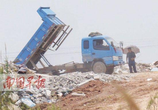 撑伞男在江边指挥货车倒垃圾。图片来源:南国早报