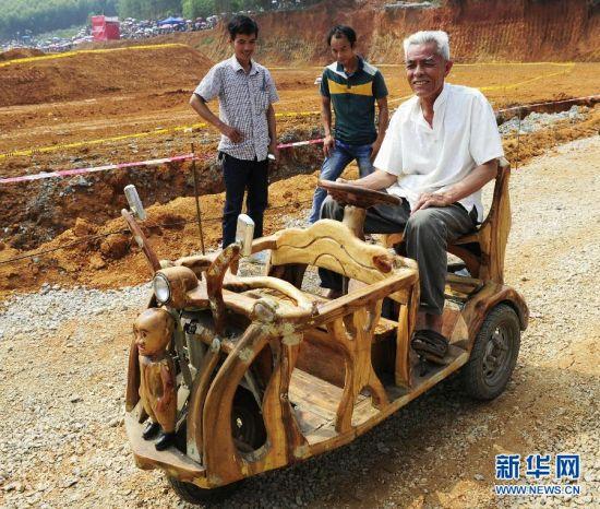 韦贵荣在驾驶自己用樟木手工打造的三轮车,车前脸的木头人眼睛会闪光。