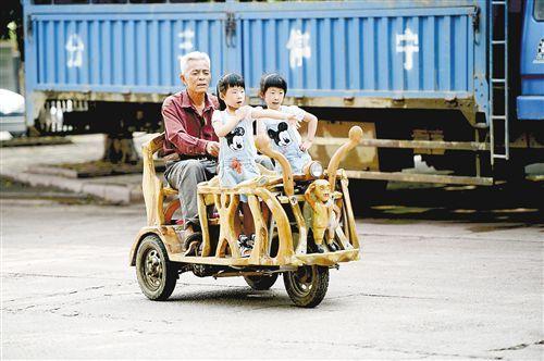 5月27日,韦贵荣用自造的三轮车接双胞胎孙女放学回家。