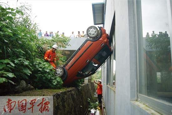 小轿车倒车翻下路边深沟。都春雷 摄