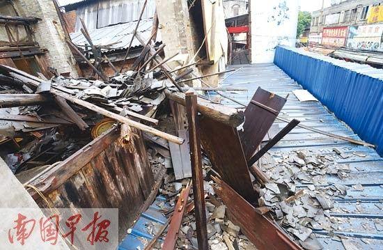 倒塌的瓦片木梁砸破楼下店面屋顶。 记者 何定坚摄