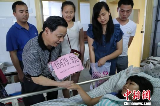 6月4日,融安县第二中学校长李建文代表全校师生将爱心捐款交给韦柳英,祝福她早日康复,重新回到课堂。 卫纲 摄