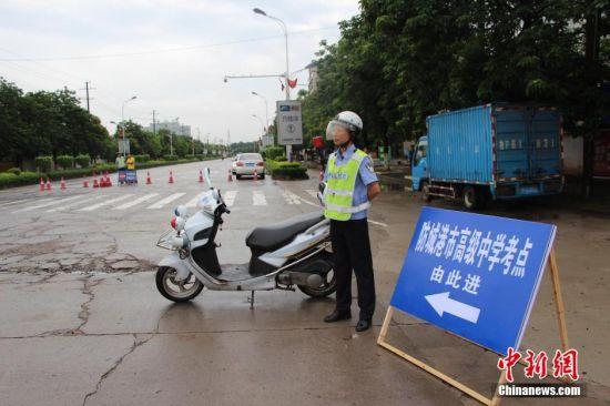 图为防城港一名交警在考点周边进行交通管制。唐任阳 摄