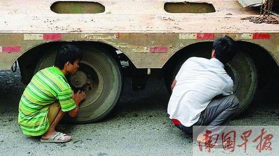 经过伙计们的一番努力,车身终于降低,但仍不能通过立交桥。记者 邹财麟摄