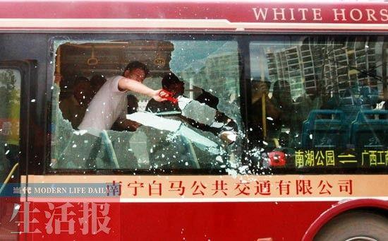 """公交车突然""""起火"""",乘客击碎玻璃窗准备跳车逃生。何学俏 摄"""