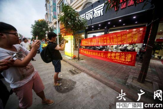 """一厨具商家打出横幅以支持""""荔枝狗肉节"""",引得民众围观拍照。"""