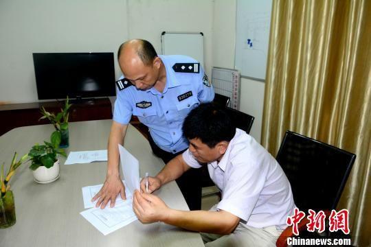 图为原广西全州县农业局局长蒋玉葵在行政处罚决定书上签字。唐梦宪摄