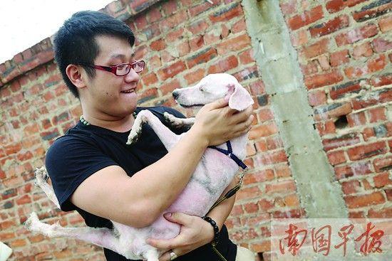 """市民杨先生见到""""好友""""KK,格外欣喜。 记者 邹财麟摄"""