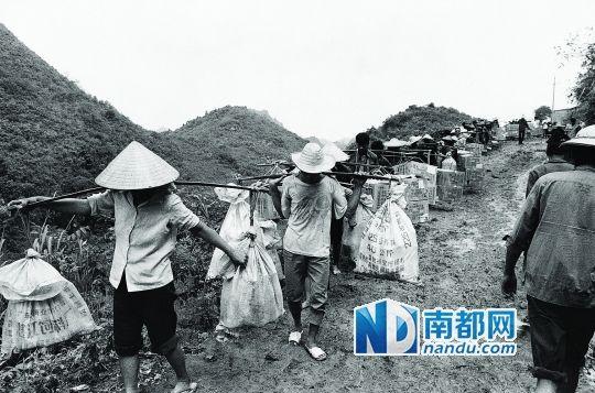 1990年,在广西凭祥的中越边境,越南的挑夫将啤酒等日用品从弄尧边境贸易市场挑往越南。安哥 摄