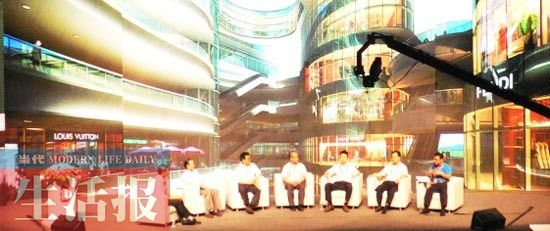 峰会上,李健(穿蓝色上衣)与专家、县长对话。