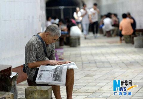 柳州市民正在防空洞里坐着看报纸。来源:新华网