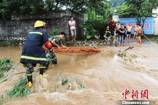 图为消防官兵携带装备进村。 韦功兵 摄