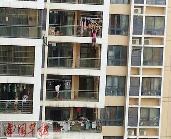 7月9日,翡翠园小区里,一名女子在阳台欲轻生时,被亲友拉住了双手。