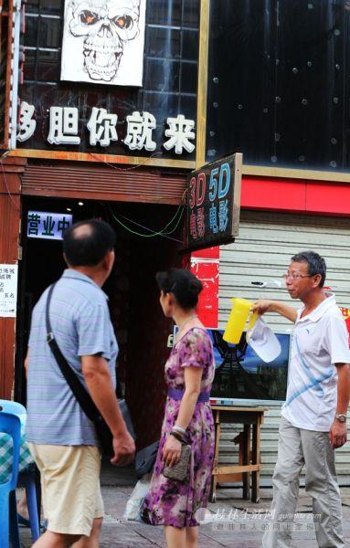 """昨日下午,正阳步行街上这家""""5D""""电影院打出广告吸引路人。记者李凯 摄"""