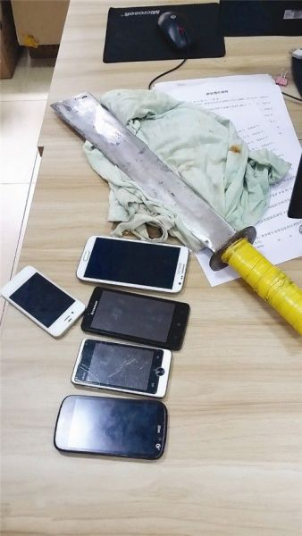 警方缴获的砍刀和手机。南国早报记者 邓晓衡摄