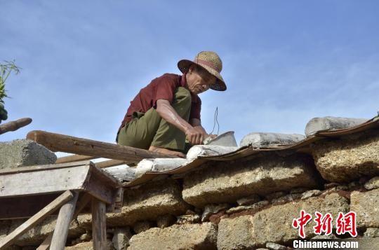 广西北海涠洲岛居民在修葺被台风损坏的房屋。 翟李强 摄